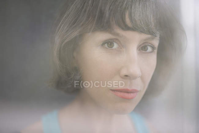 Portrait of mature woman seen through window glass — Stock Photo