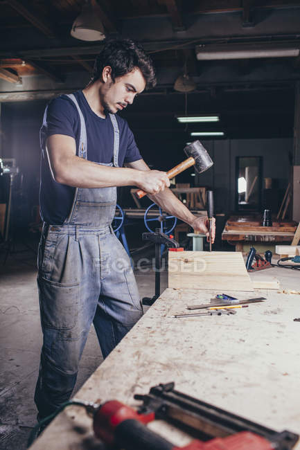 Menuisier avec marteau et ciseau sur bois à l'atelier — Photo de stock