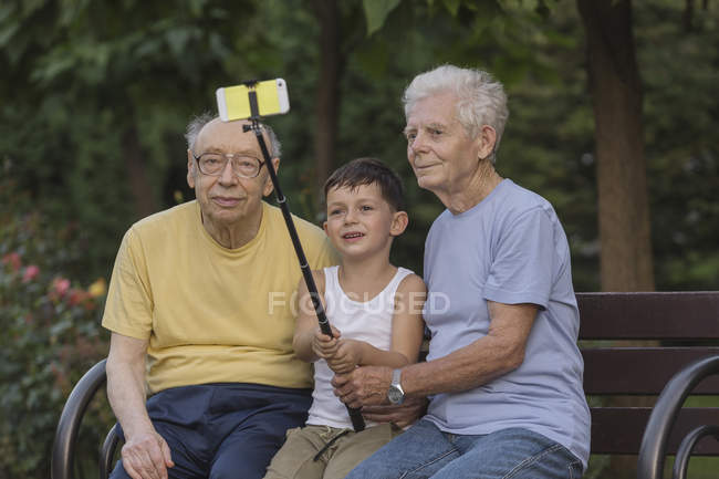 Smiling boy taking selfie with monopod with grandfathers at park bench — Stock Photo