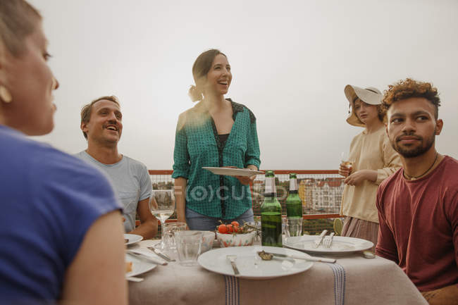 Cheerful friends enjoying lunch party on patio — Stock Photo