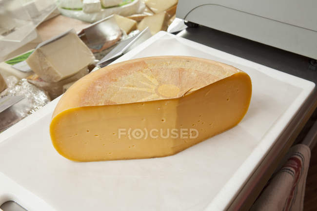 Roue de fromage cheddar sur planche à découper — Photo de stock