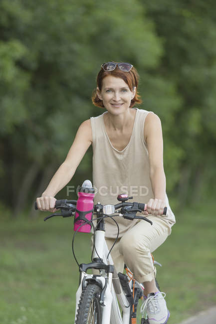Retrato de mulher sorridente andando de bicicleta no parque — Fotografia de Stock
