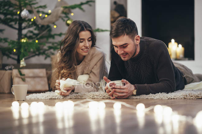 Smiling couple having coffee while lying on rug at home during Christmas — Stock Photo