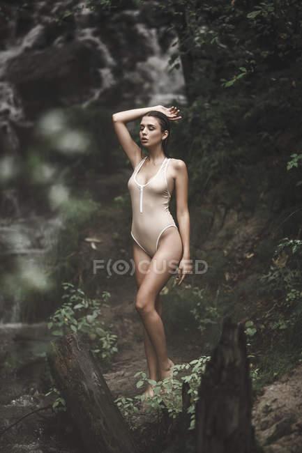 Jeune femme sensuelle en maillot de bain debout dans la forêt — Photo de stock