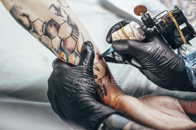 Artista che indossa guanti tatuaggio disegno sulla mano umana — Foto stock