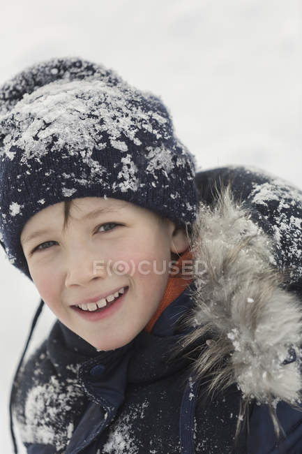 00e78291d0 Portrait of happy boy in winter wear covered with snow — looking at ...