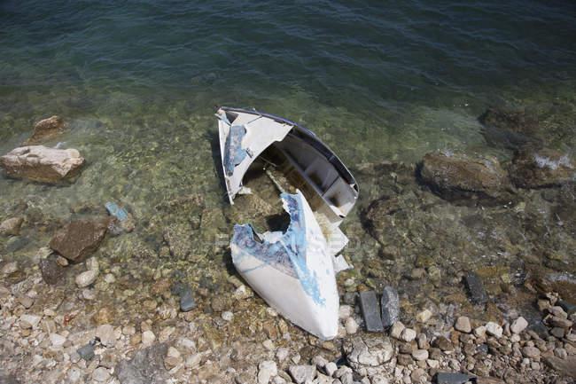 Vista ad alto angolo della barca danneggiata sulla riva — Foto stock