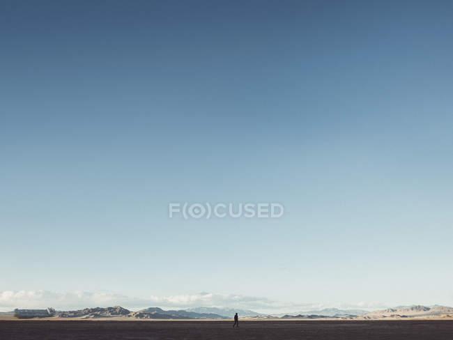 Fernsicht auf der Silhouette, die zu Fuß in der Wüstenlandschaft gegen klar blauen Himmel — Stockfoto