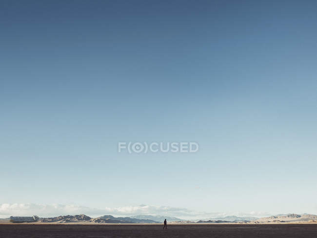 Отдаленное представление о силуэт, ходьба на ландшафт пустыни против четкие голубое небо — стоковое фото
