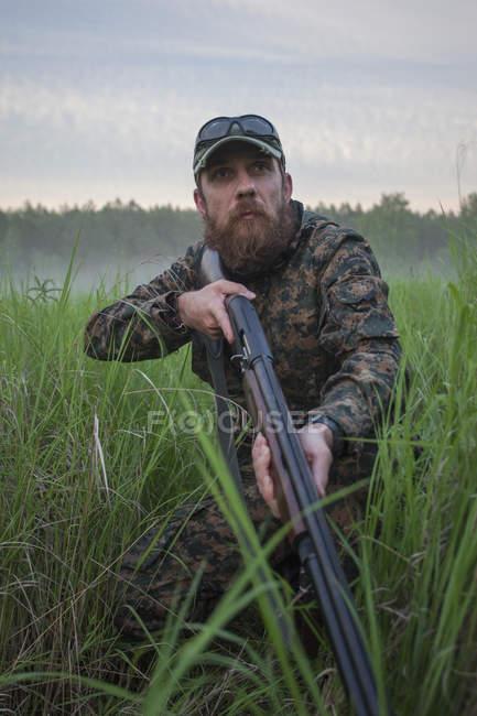 Rifle de cazador celebración mirando lejos en campo - foto de stock