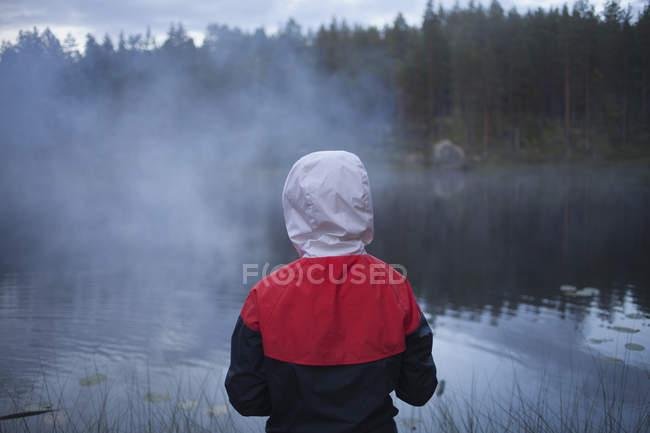 Visão traseira da criança vestindo capa de chuva no lago em tempo nebuloso — Fotografia de Stock