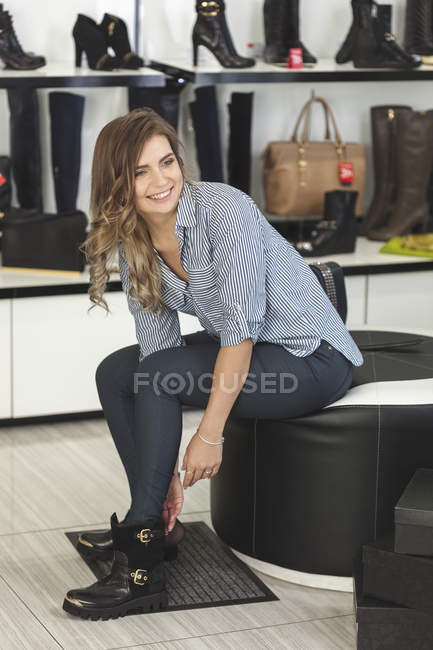 Happy woman looking away while trying on shoes at store — Stock Photo