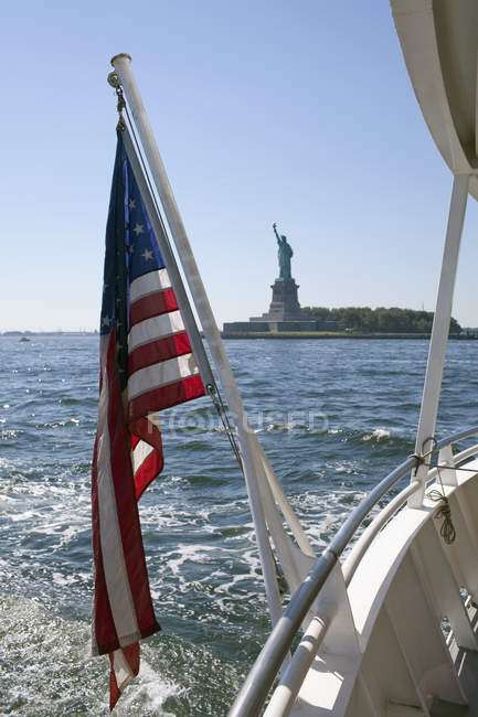 Chiuda sulla vista della bandiera americana su traghetto contro la statua della libertà nella priorità bassa — Foto stock