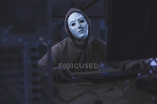 Computer hacker wearing mask and hood using computer — Stock Photo