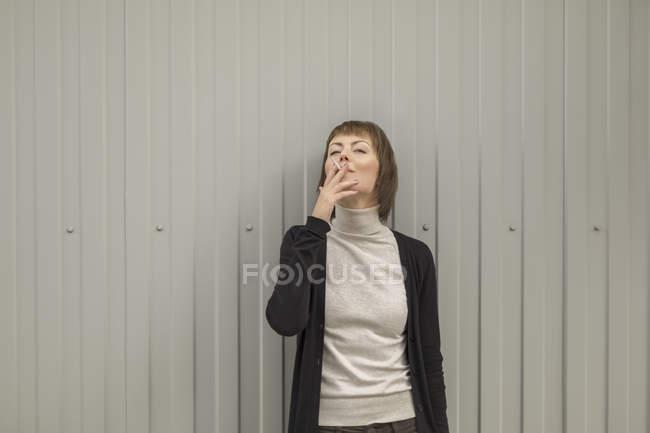 Mujer adulta fumando cigarrillo mientras está de pie contra la pared - foto de stock