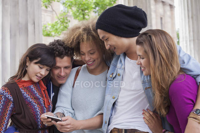Молода жінка, показуючи мобільний телефон друзям — стокове фото