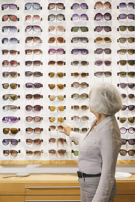 Senior woman choosing sunglasses at store — Stock Photo