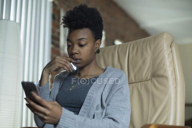 Mujer usando el teléfono móvil mientras está sentado en el sillón en casa - foto de stock