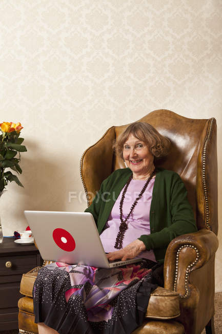 Happy senior woman using a laptop in armchair at home — Stock Photo