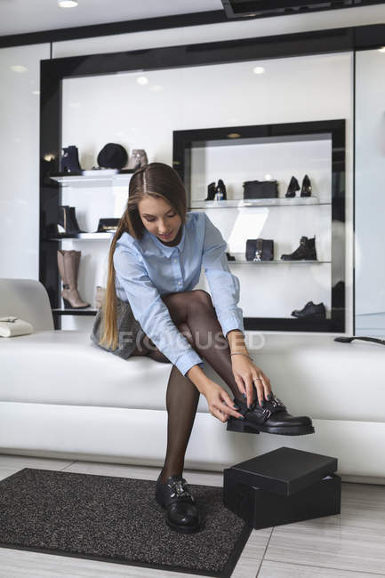 Full length of young woman trying on shoes at store — Stock Photo