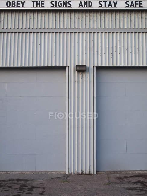 OBTENER LAS SEÑALES Y MANTENER SAFE letras en la parte superior del edificio del almacén - foto de stock