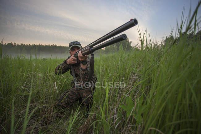 Cazador con rifle mientras de rodillas en el campo contra el cielo - foto de stock