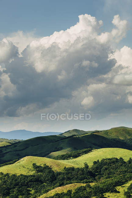 Scenic landscape of green hills and clouds in sky — Stock Photo