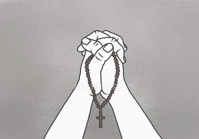 Imagen recortada de las manos apretadas sosteniendo cuentas de rosario sobre fondo gris - foto de stock