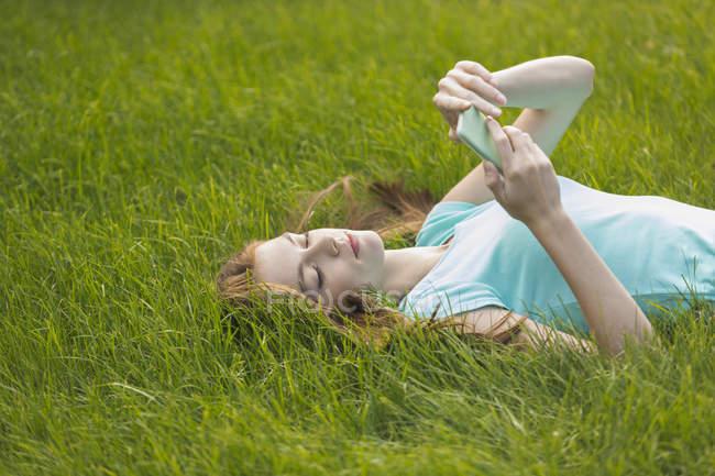 Молодая женщина использует телефон, лежа на травянистом поле — стоковое фото