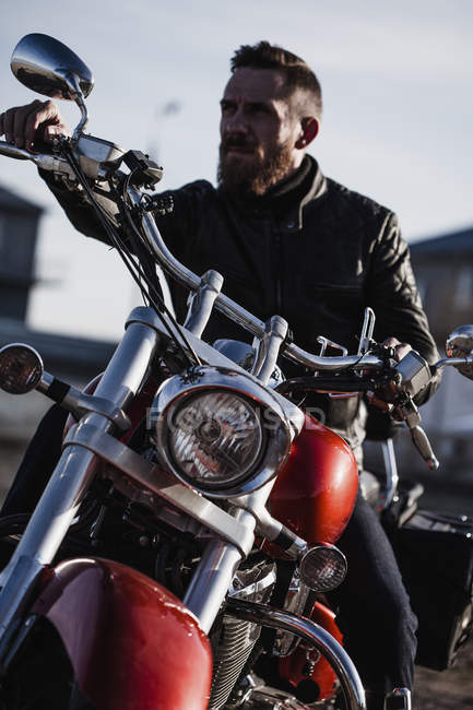 Portrait of biker sitting on motorcycle and looking away — Stock Photo