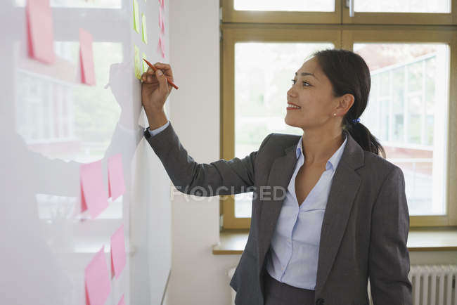 Предприниматель, писать на клей ноте, подключенным через доску в офисе — стоковое фото