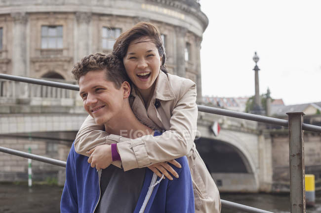 Low angle portrait of cheerful woman embracing male friend against Bode Museum, Germany — Stock Photo