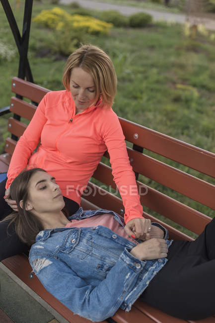Daughter lying head on mothers lap while sitting at bench in park — Stock Photo