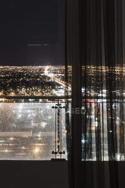 Illuminated cityscape seen through curtains on window, Las Vegas, Nevada, USA — Stock Photo
