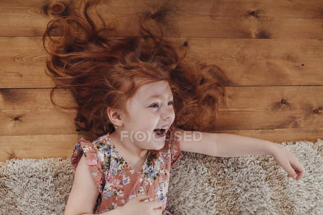 Счастливая рыжая маленькая девочка лежит на ковре в гостиной дома — стоковое фото