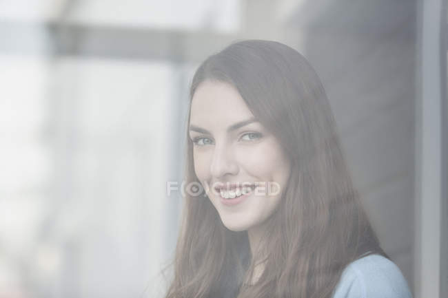 Portrait of smiling young woman seen looking through glass window — Stock Photo