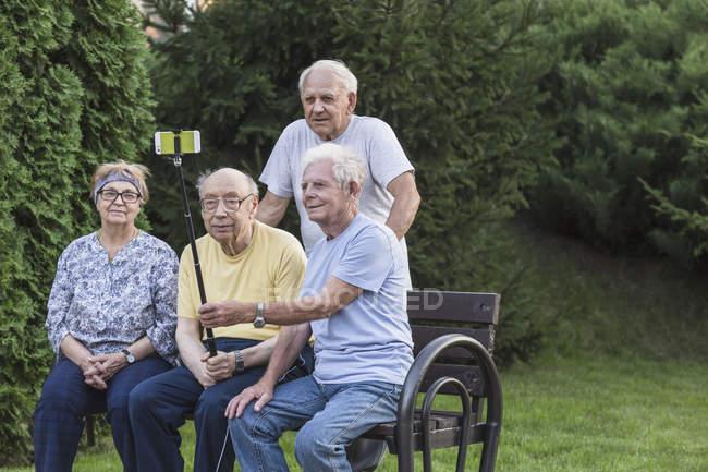 Lächelnde Senioren machen Selfie mit Einbeinstativ auf Parkbank — Stockfoto