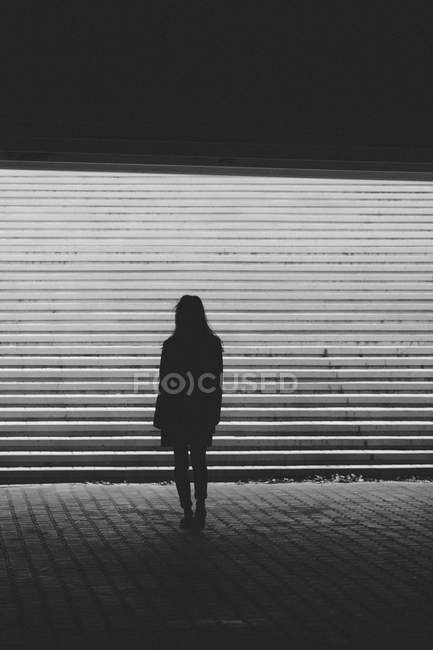 Silhouette woman standing by steps at underground passage — Stock Photo