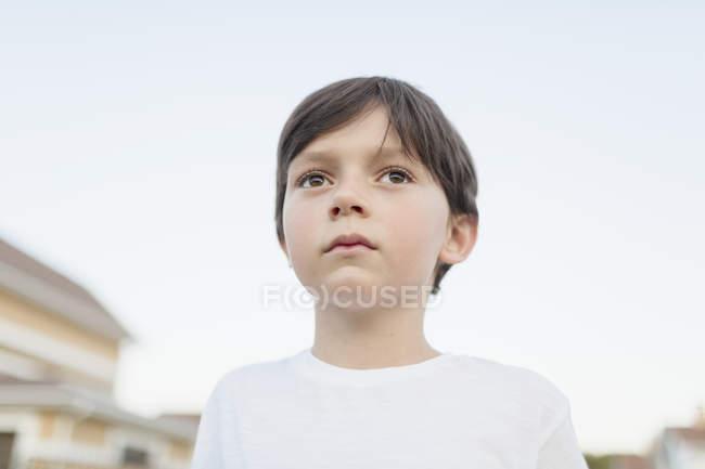 Nahaufnahme eines jungen Wegsehen stehend gegen klaren Himmel — Stockfoto
