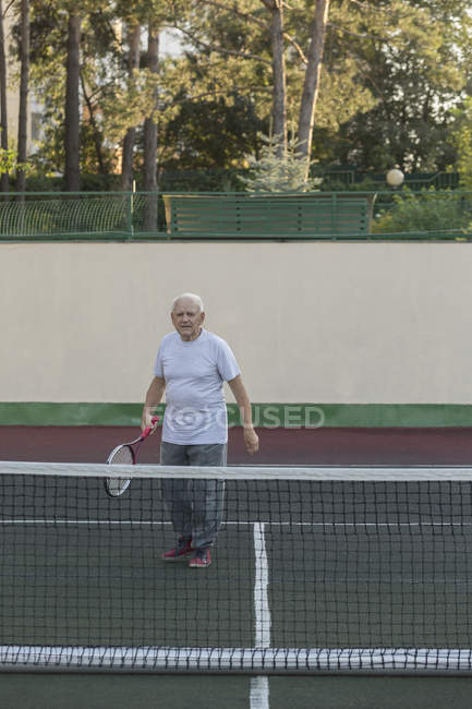 Senior man playing tennis against wall on playing field — Stock Photo