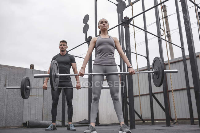 Male and female athletes lifting barbells during crossfit training — Stock Photo