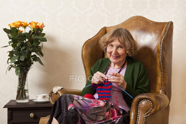 Portrait of senior woman knitting in armchair at home — Stock Photo