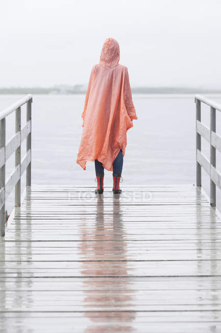 Rear view of woman wearing raincoat standing on jetty at rain — Stock Photo