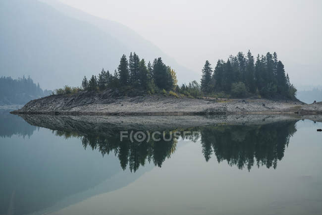 Landscape with trees on island reflecting on calm lake in foggy weather — Stock Photo