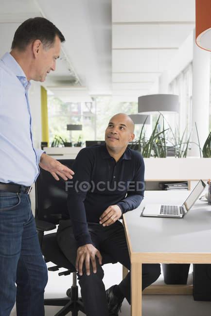 Усміхаючись впевнено бізнесменів, слухаючи чоловічого колега бюро в творчих office — стокове фото