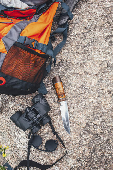 Top view of backpack with binoculars and knife on rock — Stock Photo