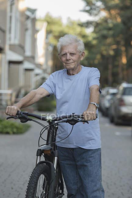 Портрет старшого дорослих стоячи з велосипеді по міській вулиці — стокове фото