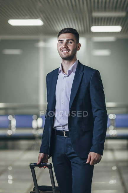 Smiling young businessman with luggage looking away at airport — Stock Photo