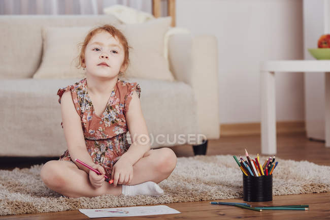 Thoughtful girl drawing while sitting on carpet in living room at home — Stock Photo