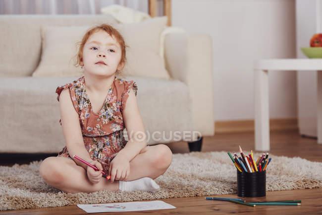 Menina pensativo desenho enquanto sentado no tapete na sala de estar em casa — Fotografia de Stock